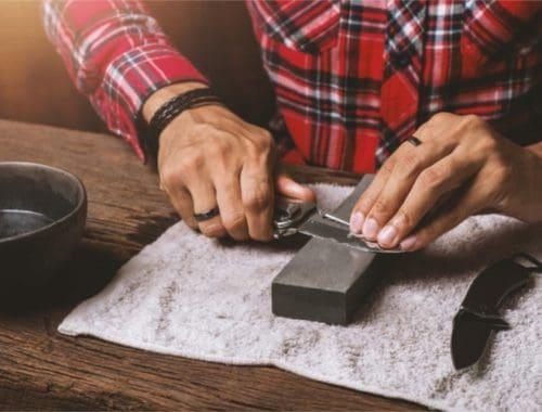 Man sharpening knife on stone
